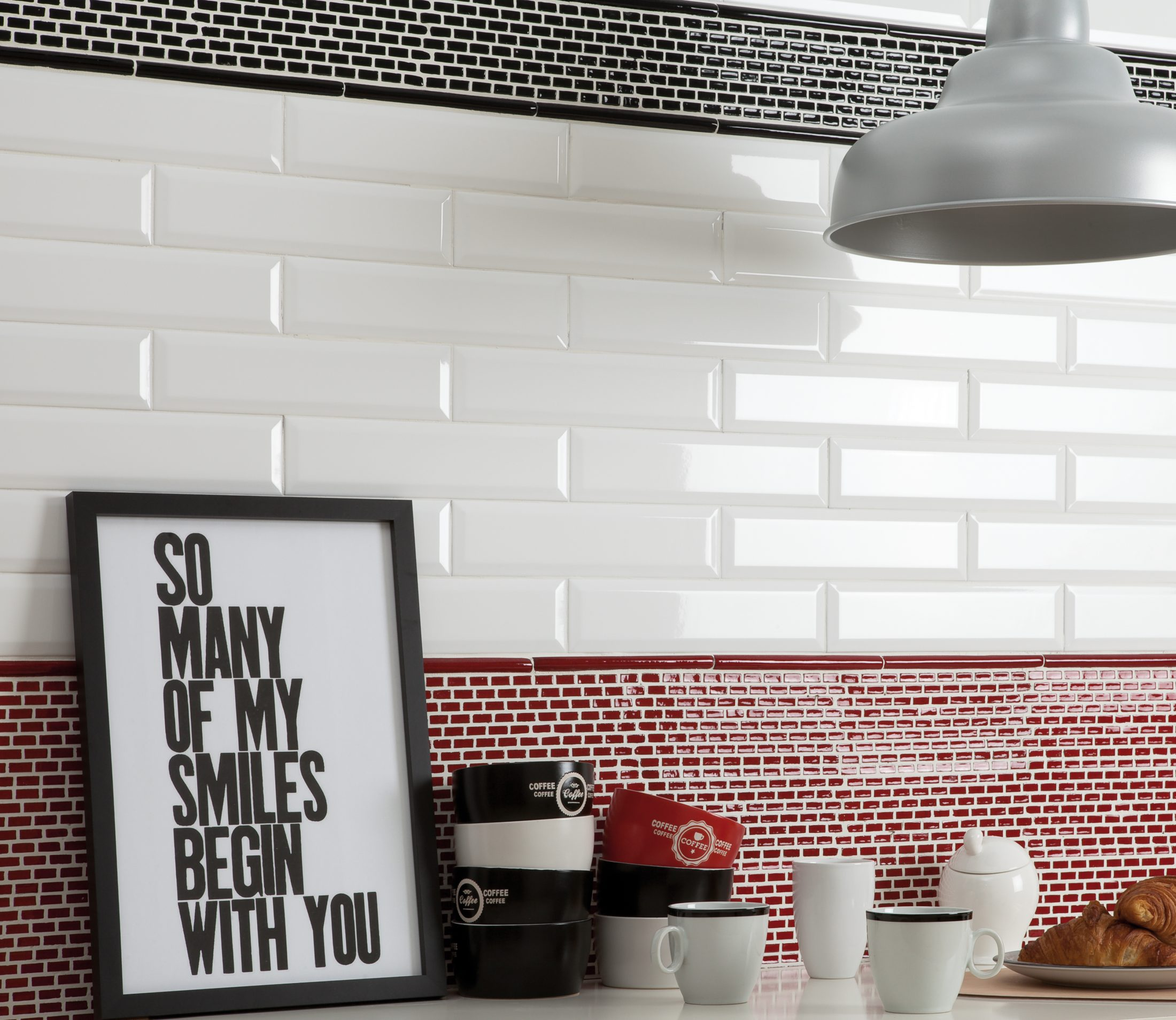 "Cevica: Mini Seriers. Intallation of white glossy subway tiles with wider length. Mini-bricks in black and red (4X10"") Trim: Listelo Pencil Mini in red and black (.5X8"")"